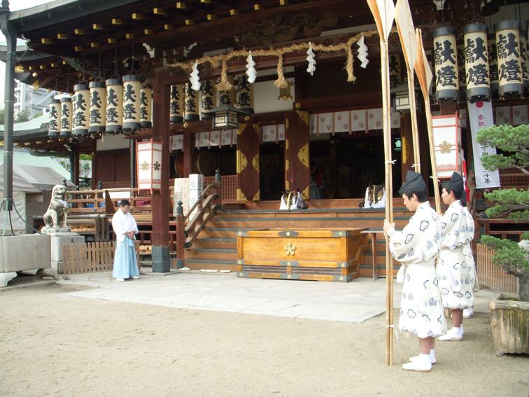本殿で祝詞中。右側にいる人が掲げているのが的